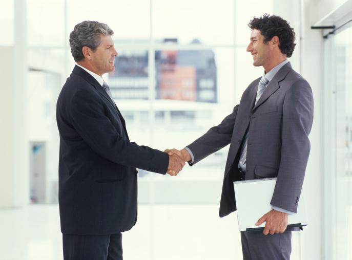 deux hommes se serrent la main pour leur contrat de déménagement